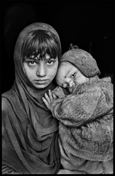 AFGHN-13198; Afghanistan; 1980. A young girl holds her sibling.